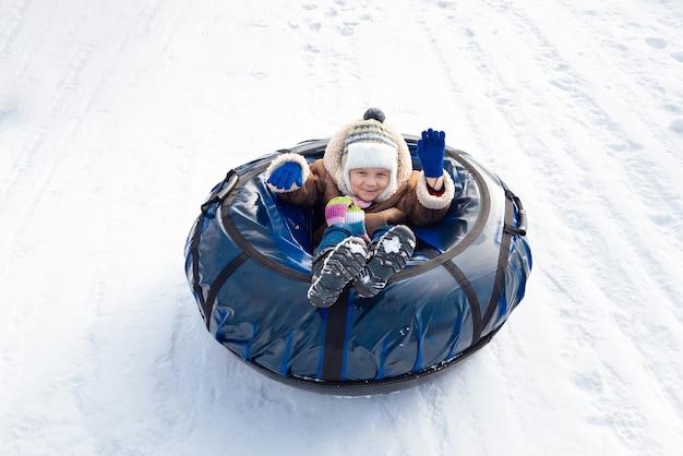 Criança feliz sentada em um tubo e acenando com a mão