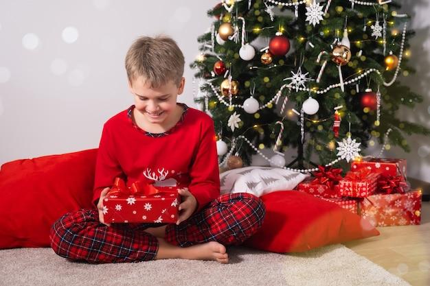 Criança feliz sentada no chão em casa segurando um presente de natal perto da árvore de natal