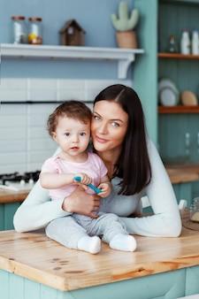 Criança feliz, sentado na cozinha à mesa com a mãe segurando uma colher na mão