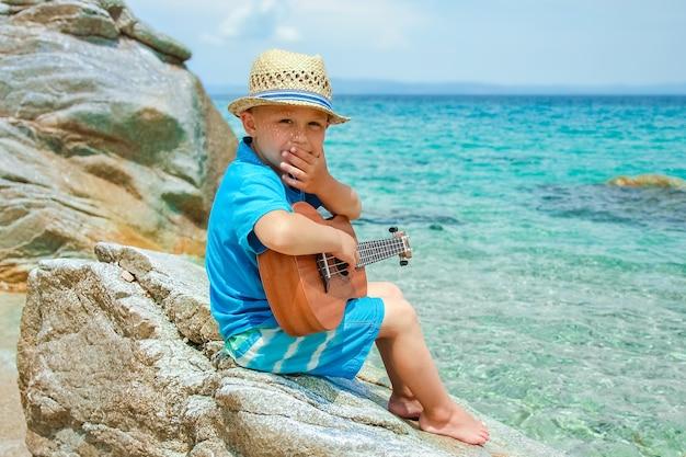 Criança feliz tocando guitarra à beira-mar da grécia no fundo da natureza