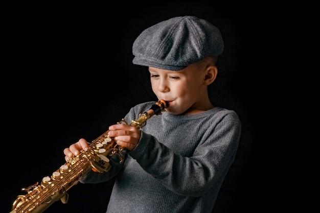 Criança feliz tocando saxofone no estúdio