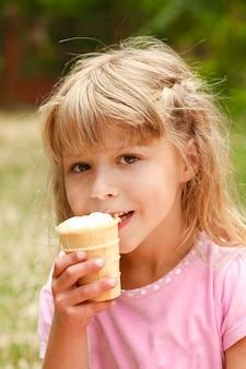 Criança feliz tomando sorvete ao ar livre no parque