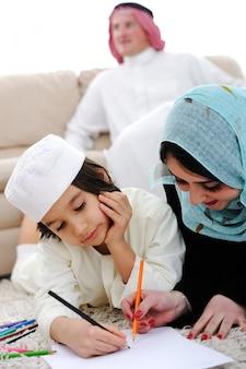 Criança feliz trabalhando na lição de casa em casa com sua família