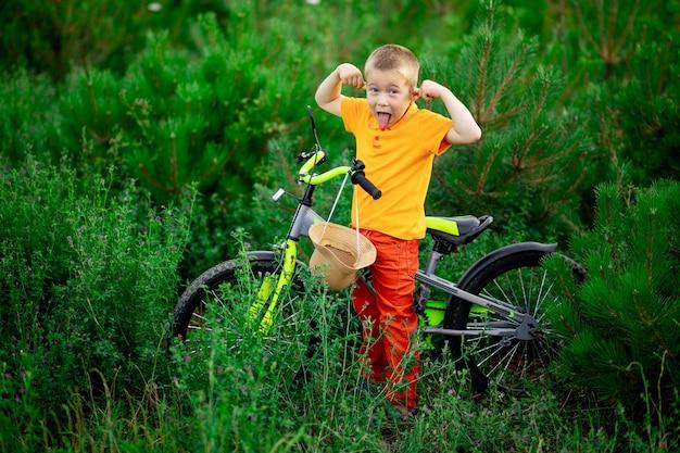 Criança feliz, um menino com roupas laranja e uma bicicleta brincando na grama verde no verão