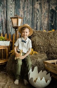 Criança feliz, um menino de corpo inteiro com cabelo castanho e um chapéu de palha está sentado no feno com um patinho. comemorando a páscoa com as crianças