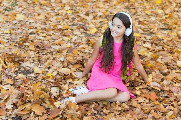 Criança feliz usa fones de ouvido enquanto relaxa nas folhas de outono, música.