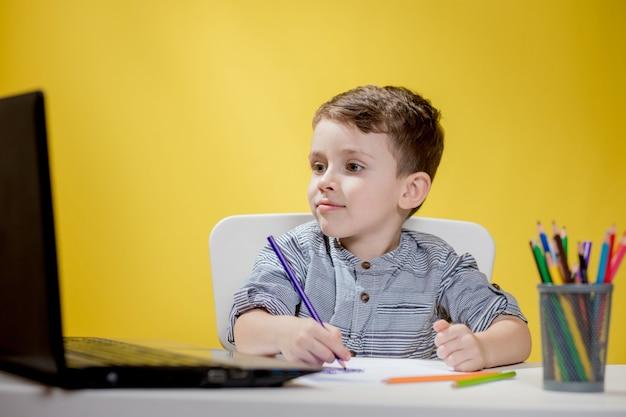 Criança feliz usando laptop digital fazendo lição de casa em amarelo. distanciamento social, educação online e-learning.