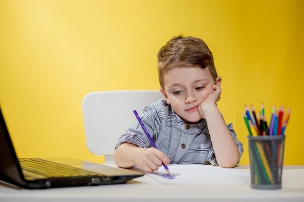 Criança feliz usando laptop digital, fazendo lição de casa na parede amarela. distanciamento social, educação online de e-learning.