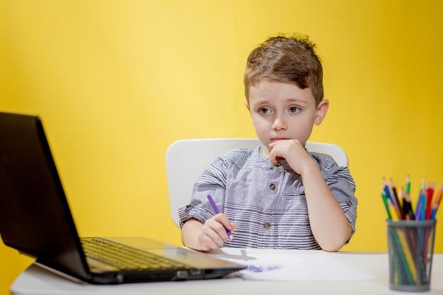 Criança feliz usando laptop digital fazendo lição de casa sobre fundo amarelo