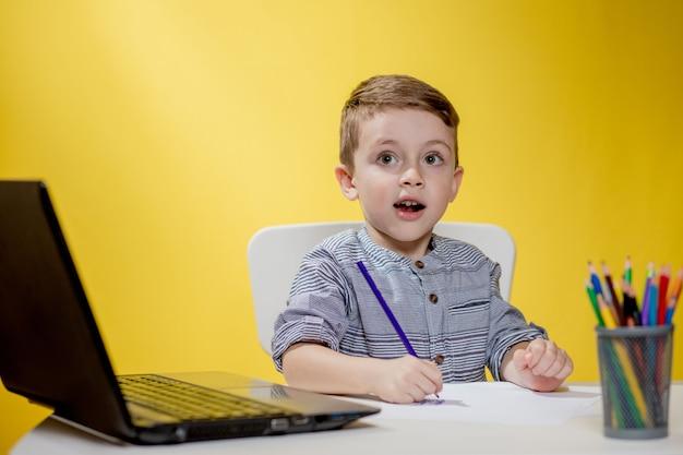Criança feliz usando laptop digital, fazendo lição de casa sobre fundo amarelo.