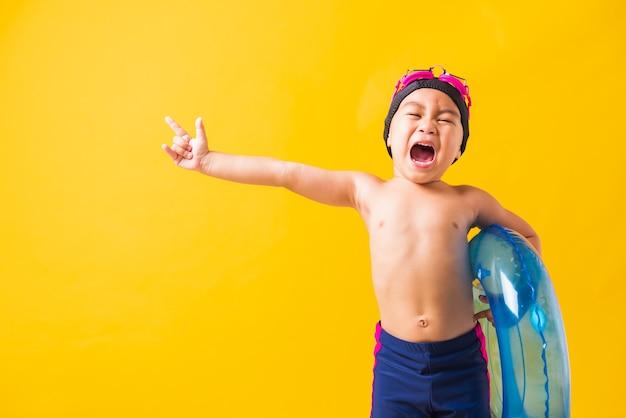Criança feliz usando óculos e maiô segurando um anel inflável azul
