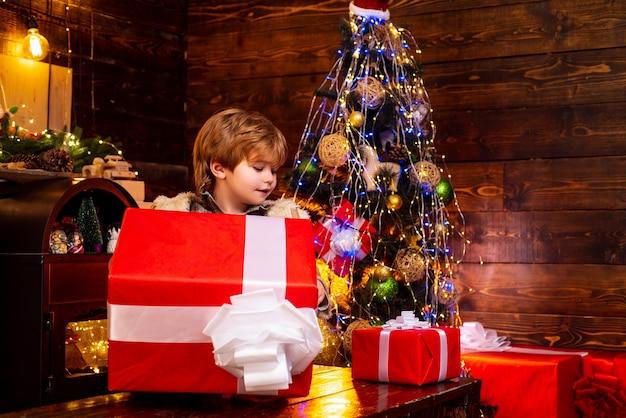 Criança feliz vestida com roupas de inverno, pense no papai noel perto da árvore de natal natal crianças ...