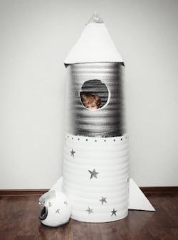 Criança feliz vestida com uma fantasia de astronauta, brincando com um foguete feito à mão.