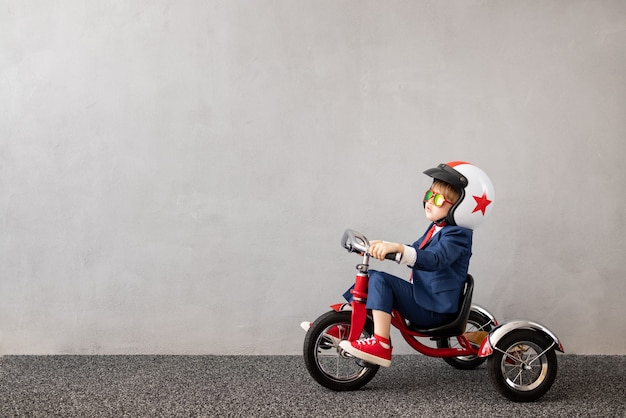 Criança feliz vestindo terno andando de bicicleta contra a parede de concreto cinza. sonhos de infância e conceito de ideia de negócio