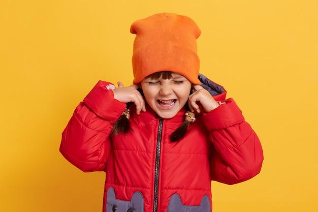 Criança feliz vestindo um traje casual quente, cobrindo as orelhas com os dedos e rindo alegremente