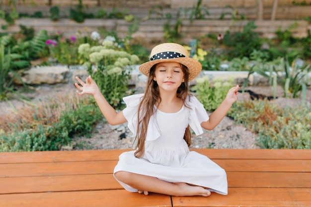 Criança feminina bonita morena com chapéu de palha, sentada perto do canteiro de flores em pose de lótus, com os olhos fechados. menina de vestido branco fazendo ioga no jardim