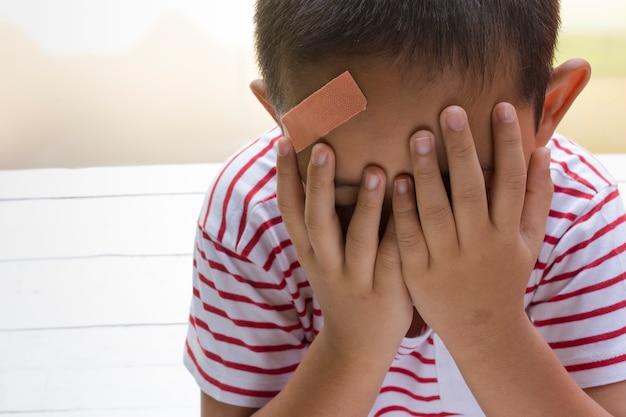 Criança ferida na cabeça com fundo branco de madeira