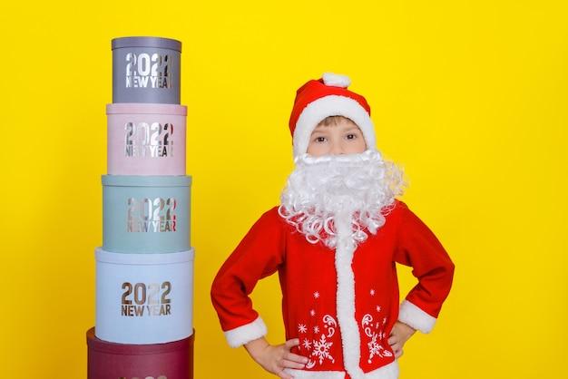 Criança fica ao lado de uma torre de caixas redondas com ano novo 2022, ela está vestida com fantasia de papai noel