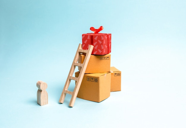Criança fica perto de uma caixa de presente em uma pilha de caixas. o conceito de encontrar o presente perfeito.