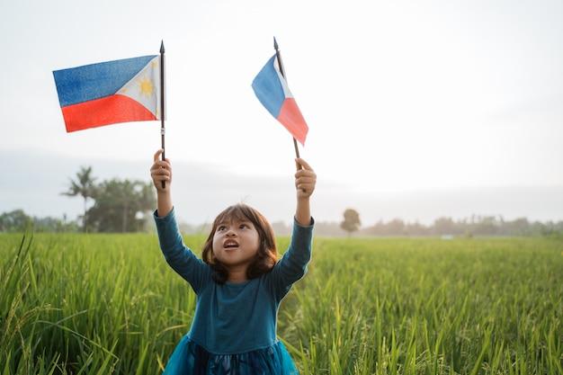 Criança filipina com bandeira nacional