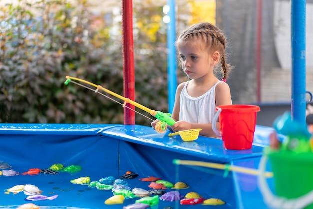 Criança fisher pegando peixe de brinquedo de plástico na piscina parque de diversões dia de verão menina se divertindo na pesca festival de carnaval de entretenimento para crianças