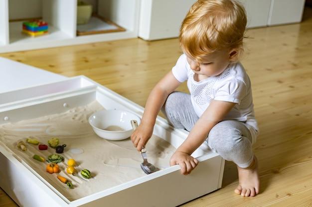 Criança fofa brincando de autodesenvolvimento em casa caixa de areia cinética usando o método maria montessori