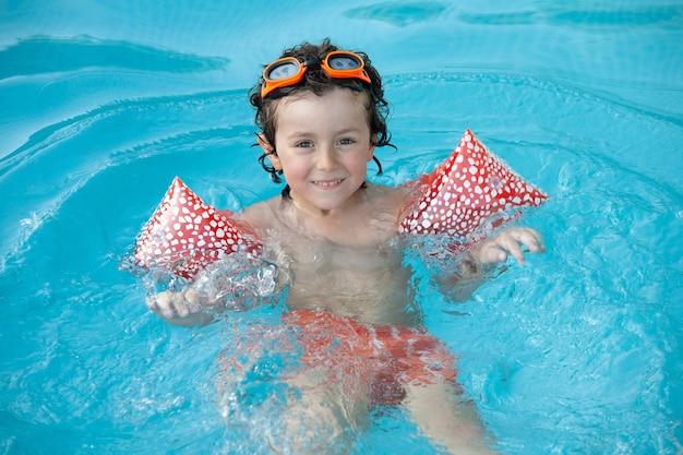 Criança fofa brincando na piscina com óculos laranja