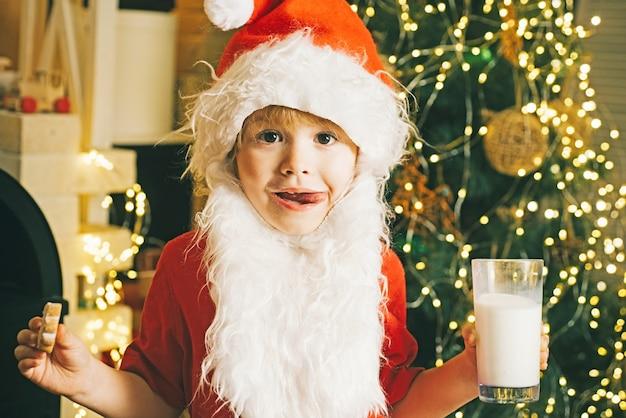 Criança fofa com chapéu de papai noel comendo biscoitos e bebendo leite