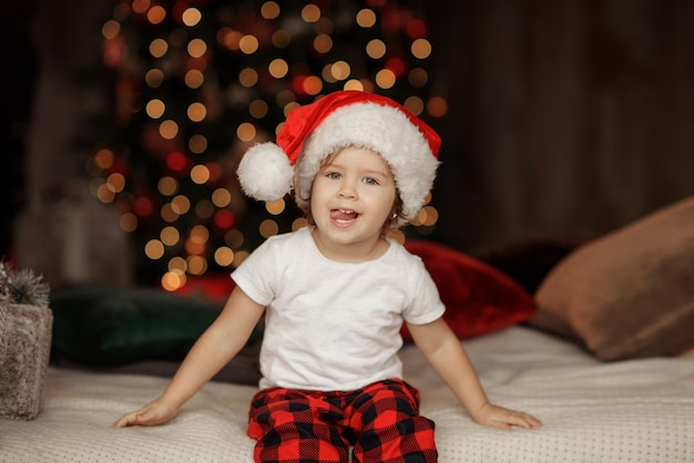 Criança fofa com chapéu de papai noel sentado em uma poltrona grande e aconchegante na sala de estar