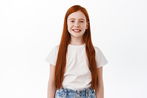 Criança fofa com longos cabelos vermelhos sorrindo e parecendo feliz na frente, em pé sobre uma parede branca