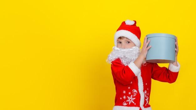 Criança fofa com roupas de papai noel e barba branca segurando uma caixa redonda de presente no alto das mãos.