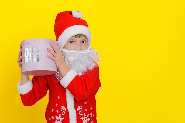 Criança fofa com roupas de papai noel e com barba segurando uma caixa de presente redonda rosa com nas mãos
