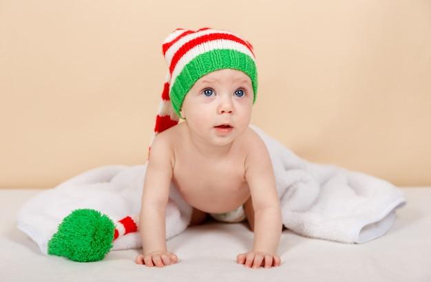Criança fofa com um chapéu de papai noel de crochê