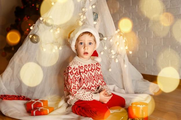Criança fofa e alegre brincar perto da árvore de natal, é um milagre
