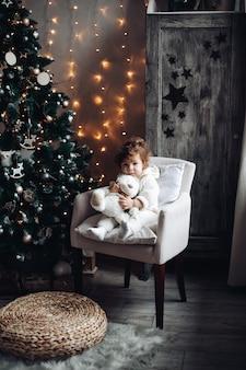 Criança fofa e cacheada com um urso de pelúcia sentado em uma poltrona perto de uma árvore de natal lindamente decorada