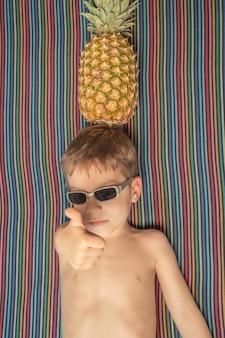 Criança fofa e feliz com óculos escuros e abacaxi na cabeça tomando banho de sol em uma toalha listrada