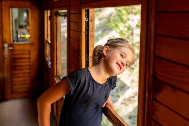 Criança fofa olhando pela janela de um trem