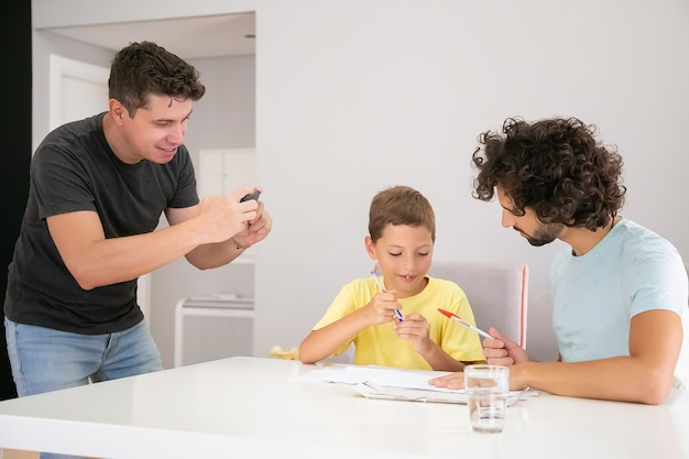 Criança fofa positiva fazendo tarefas escolares em casa com a ajuda de dois pais, escrevendo nos jornais. homem tirando foto de sua família. conceito de família e pais gays