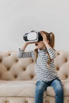 Criança fofa usando fone de ouvido de realidade virtual e sentada no sofá