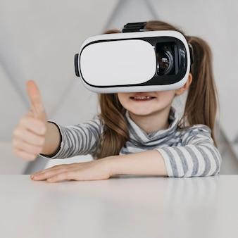 Criança fofa usando fone de ouvido de realidade virtual, polegar para cima