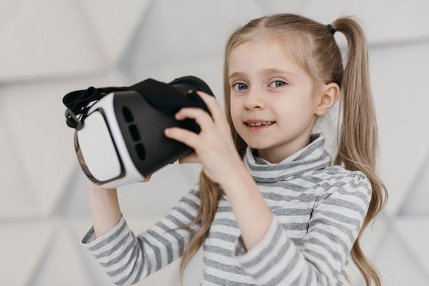 Criança fofa usando fone de ouvido de realidade virtual