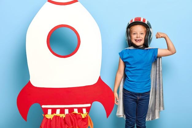 Criança forte usa capacete e capa de proteção, mostra bíceps