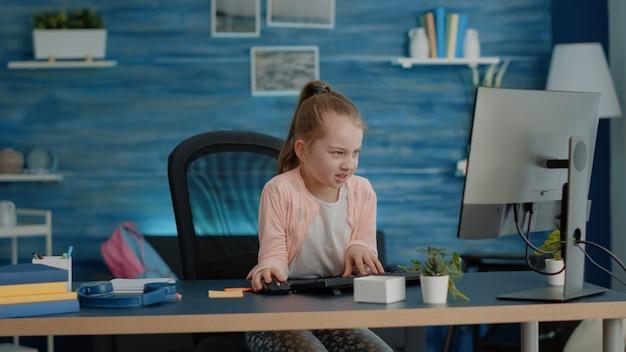 Criança frustrada frequentando aulas online no computador