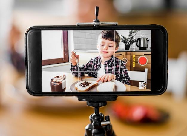 Criança gravando-se com telefone