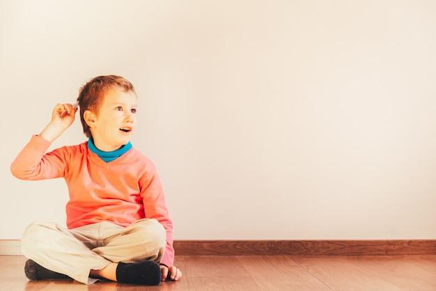 Criança independente de 5 anos penteando-se sentado no chão de sua casa