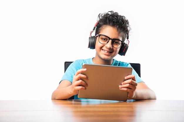 Criança indiana asiática brincando ou estudando em um computador tablet, sem fio