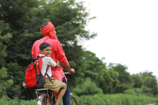 Criança indiana brincando com o avião de brinquedo com o pai na bicicleta