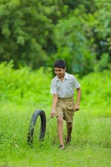 Criança indiana brincando com o pneu no campo