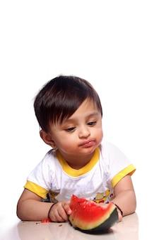 Criança indiana comendo melancia