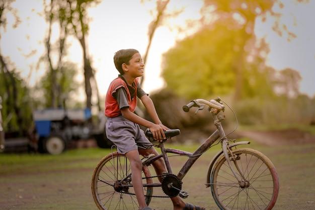 Criança indiana em bicicleta, jogando no exterior
